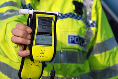 Breathalyser. Police officer holds breath test device; very useful for editorial features relating anti drinking and driving articles