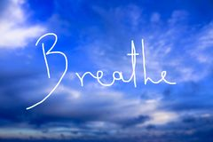 Breathe Handwritten logo in the sky. A handwritten logo as a reminder to breathe consciously and use the breath as a mean for healing and relaxation Royalty Free Stock Image