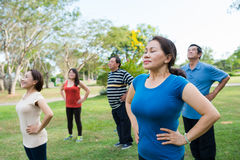 Breathing deeply. Mature people standing and breathing deeply at outdoor yoga class stock images