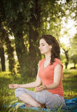 Breathing Exercise. Young woman in lotus position trying a breathing exercise in nature Stock Photos
