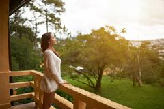 Breathing fresh air. Beautiful Asian woman breathing fresh air on villa balcony in morning Royalty Free Stock Images