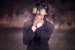 Breathless person in the forest fire. Young man in formal suit wearing a gas mask and looks chokes in the forest fire Stock Photo