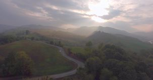 Countryside road aerial view. Breathtaking aerial drone footage: Flight over autumn trees, meadows in sunset soft light and haze. Majestic landscape, flying over stock video