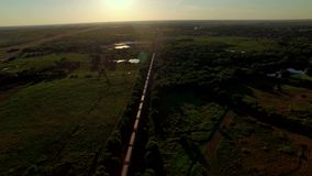 Breathtaking aerial of a freight train passing through countryside. A dizzying and breathtaking aerial of a freight container train passing through countryside stock video footage