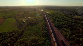 Breathtaking aerial of a freight train passing through countryside. A dizzying and breathtaking aerial of a freight container train passing through countryside stock footage