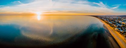 Аerial panorama of sun setting over smooth water. Breathtaking aerial panorama of sun setting over smooth water surface with cloud reflections Royalty Free Stock Photo