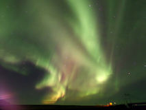 Breathtaking green and pink Aurora Borealis flashing on the night sky Stock Photos