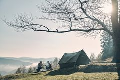 Breathtaking landscape. Young couple having morning coffee while. Camping in mountains Stock Photography