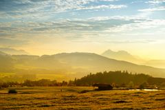 Breathtaking lansdcape of Austrian countryside on sunset. Dramatic sky over idyllic green fields of Anstrian Central Alps on autum Royalty Free Stock Photo