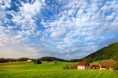 Breathtaking lansdcape of Austrian countryside on sunset. Dramatic sky over idyllic green fields of Anstrian Central Alps on autum Stock Images