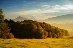Breathtaking lansdcape of Austrian countryside on sunset. Dramatic sky over idyllic green fields of Anstrian Central Alps on autum. Breathtaking lansdcape of Royalty Free Stock Photography