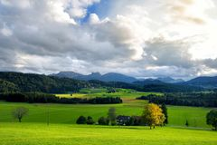 Breathtaking lansdcape of mountains, forests and small Bavarian villages in the distance. Scenic view of Bavarian Alps with majest. Ic mountains in the Stock Photography