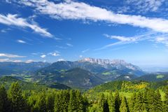 Breathtaking lansdcape of mountains, forests and small Bavarian villages in the distance. Scenic view of Bavarian Alps with majest. Ic mountains in the Stock Image
