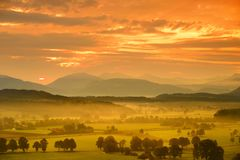 Breathtaking morning lansdcape of small bavarian village covered in fog. Scenic view of Bavarian Alps at sunrise with majestic mou Royalty Free Stock Photography