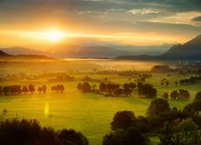Breathtaking morning lansdcape of small bavarian village covered in fog. Scenic view of Bavarian Alps at sunrise with majestic mou. Ntains in the background Royalty Free Stock Photography