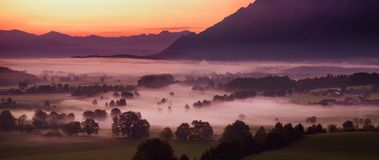 Breathtaking morning lansdcape of small bavarian village covered in fog. Scenic view of Bavarian Alps at sunrise with majestic mou. Ntains in the background Stock Images
