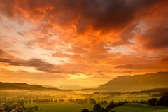Breathtaking morning lansdcape of small bavarian village covered in fog. Scenic view of Bavarian Alps at sunrise with majestic mou Stock Images