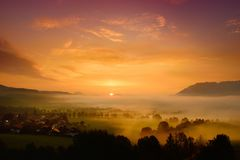 Breathtaking morning lansdcape of small bavarian village covered in fog. Scenic view of Bavarian Alps at sunrise with majestic mou Stock Photography