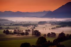 Breathtaking morning lansdcape of small bavarian village covered in fog. Scenic view of Bavarian Alps at sunrise with majestic mou Royalty Free Stock Images