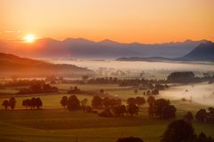Breathtaking morning lansdcape of small bavarian village covered in fog. Scenic view of Bavarian Alps at sunrise with majestic mou. Ntains in the background Stock Photo