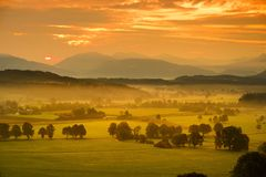 Breathtaking morning lansdcape of small bavarian village covered in fog. Scenic view of Bavarian Alps at sunrise with majestic mou. Ntains in the background Royalty Free Stock Photos