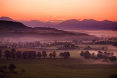 Breathtaking morning lansdcape of small bavarian village covered in fog. Scenic view of Bavarian Alps at sunrise with majestic mou. Ntains in the background Royalty Free Stock Photo
