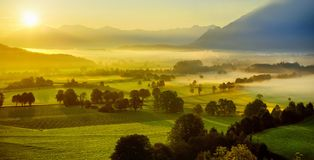 Breathtaking morning lansdcape of small bavarian village covered in fog. Scenic view of Bavarian Alps at sunrise with majestic mou Royalty Free Stock Image