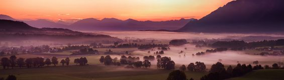 Breathtaking morning lansdcape of small bavarian village covered in fog. Scenic view of Bavarian Alps at sunrise with majestic mou. Ntains in the background Stock Photos