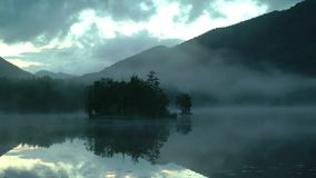 Breathtaking panorama of a beautiful quiet mountain lake. Small island on the lake surrounded by mist stock video footage