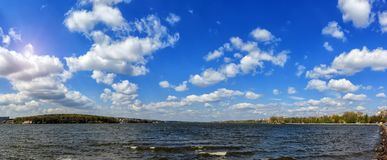 Breathtaking scenery. many fluffy clouds in the blue sky over the water. hectic urban lake. Panorama Stock Images