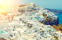 Breathtaking scenery of Oia village traditional Greek island architecture at Aegean sea and noon zenith sun flare Royalty Free Stock Images
