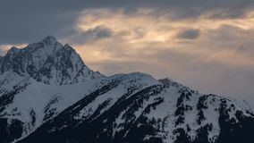 Ridgeline. Breathtaking snow capped mountain ridgeline at sunset, with a mountain peak on the left side Royalty Free Stock Image