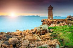 Fantastic Atlantic ocean coast in Brittany region, Ploumanach, France, Europe. Breathtaking sunset with lighthouse of Ploumanach Mean Ruz in Perros-Guirec on Royalty Free Stock Photos