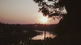A breathtaking view of the evening sunset. A beautiful disc of the sun over the river. Beautiful view of a beautiful sunset over the river in motion. Beautiful stock footage