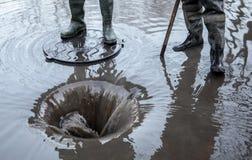 Brecha en un tubo de calefacción Trabajadores en agua drenada botas Foto de archivo libre de regalías