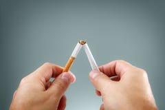 Brechen einer Zigarette Stockfoto