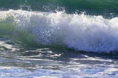 Brechende Wellen auf Mittelmeerufer stockbild