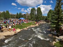 Downtown Breckenridge, Colorado - 4th of July Parade. BRECKENRIDGE, CO: Vacationers relax along the Blue River at Breckenridge`s Riverwalk Center on July 4, 2016 stock image