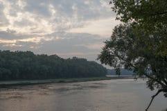 Bred flod som flödar över grön skognedgång afton Reflexioner av träd i det lugna vattnet sundown royaltyfri bild