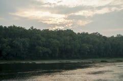 Bred flod som flödar över grön skognedgång afton Reflexioner av träd i det lugna vattnet sundown royaltyfria bilder
