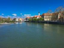 Bred flod som flödar till och med stad i sommar Arkivbild