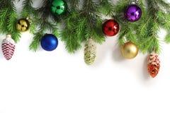 Bred jul gränsar, isolerat på vit som består av nya granfilialer av grankottar och julbollar arkivfoton