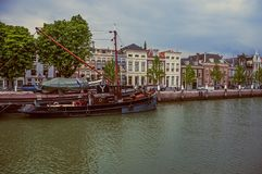 Bred kanal med tegelstenbyggnad bredvid den och massor av förtöjde fartyg i en molnig dag på Dordrecht royaltyfri foto