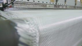Bred linne för syntetiskt tyg flyttar sig från vävstolslutsikt lager videofilmer