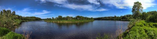 Bred panorama av en flod och de forested bergen Fotografering för Bildbyråer