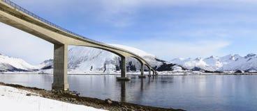 Bred panoramautsikt av bron i de Lofoten öarna i vinter med bergreflexion i fjorden royaltyfri foto