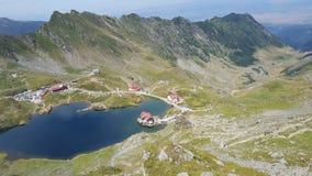 Bred sikt av bergdalen, stugor och den alpina sjön Arkivbild