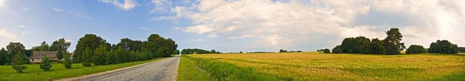 Bred sikt för panorama- bygd av vägen med träd och byn bakom lantlig sommar för liggande Typisk europeiskt herde- fält fotografering för bildbyråer