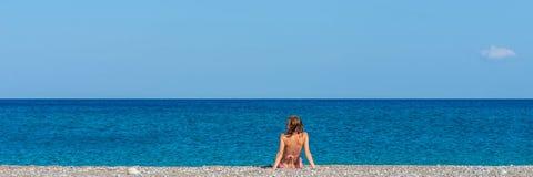 Bred siktsbild av den unga kvinnan i rosa solbada för bikini arkivfoto