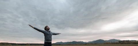 Bred siktsbild av den unga mannen som firar liv arkivfoto